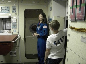 Astronaut Tracy Caldwell Dyson explains to Tyler how astronauts sleep, eat, and use the bathroom onboard the International Space Station during a tour of the Russian FGB Habitability Module. Tyler was a tad bit grossed out when he learned that astronauts drink water reclaimed and purified from urine.